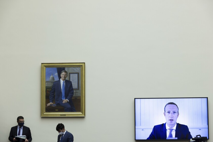 Mark Zuckerberg is shown testifying via video link before Congress next to a painting as workers in masks mill about.