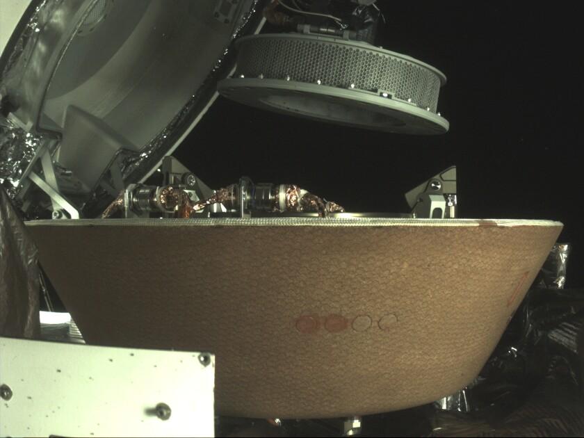 Un contenedor de muestras sobrevuela una cápsula en la nave espacial Osiris-Rex