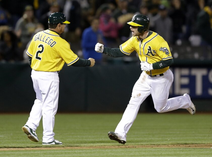 Oakland Athletics' Brett Lawrie, right, celebrates with third base coach Mike Gallego after Lawrie hit a two-run home run off New York Yankees' Jacob Lindgren in the eighth inning of a baseball game Friday, May 29, 2015, in Oakland, Calif. (AP Photo/Ben Margot)