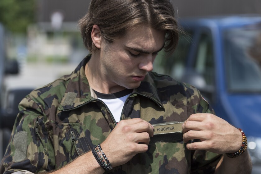 21 year old Swiss Ice Hockey player Nico Hischier, center at NHL club New Jersey Devils, placed the name tag onto the jacket of the Swiss army uniform he was just issued in Wangen an der Aare, Switzerland, Tuesday, June 16, 2020. Hischier completes part of his mandatory army service for elite athletes with an 18 week recruit training. (Alessandro della Valle/Keystone via AP)