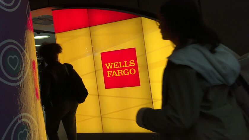 Commuters walk by a Wells Fargo ATM location at New York's Penn Station on Oct. 13, 2016.
