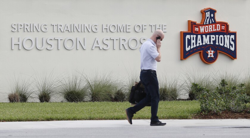 Houston Astros senior director of business operations Dan O'Neill walks past signs outside of the Houston Astros spring training baseball facility on Feb. 12.