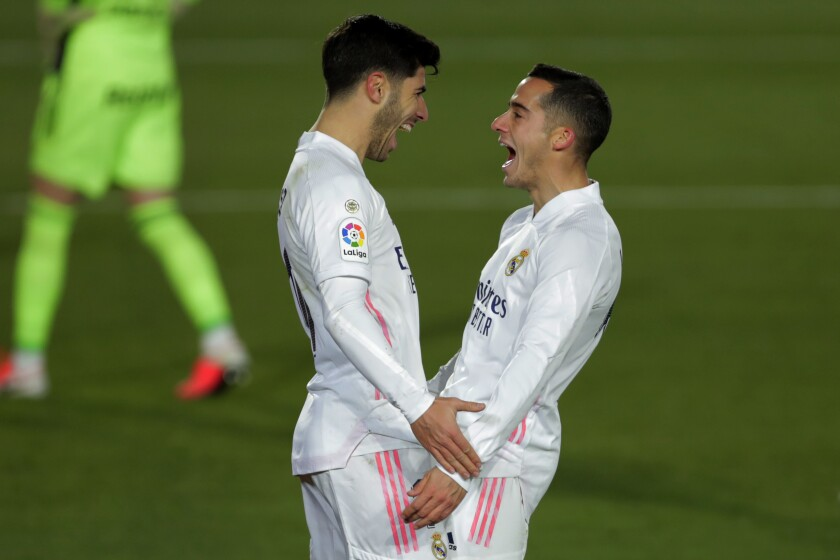 Real Madrid's Marco Asensio, left, celebrates with teammate Lucas Vazquez after scoring his side's second goal during the Spanish La Liga soccer match between Real Madrid and Celta Vigo at the Alfredo Di Stefano stadium in Madrid, Spain, Saturday, Jan. 2, 2021. (AP Photo/Manu Fernandez)