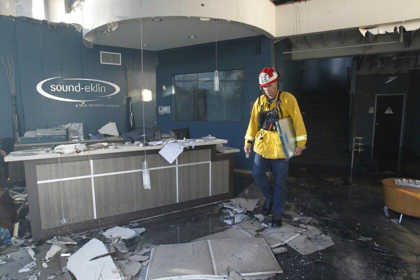 A fireman surveys the damage to Sound-Elkin Thursday morning, a company in Carlsbad damaged by the Poinsettia Fire. John Gibbins / U-T