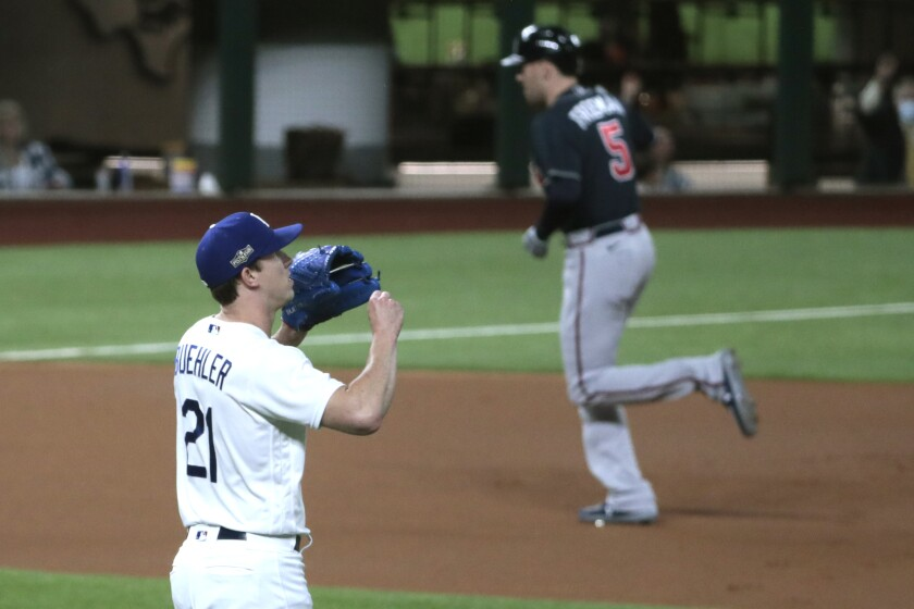 Walker Buehler tries not to look as Freddie Freeman rounds the bases on a first-inning homer.