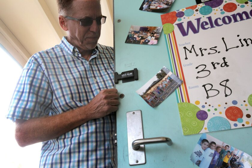 Rick Morris shows off his Lock Blok, the small black device near his right hand, that helps to diminish noise from the door handle below on a schoolroom door at Curie Elementary School in University City when the door opens and closes throughout the school day. photo by Bill Wechter