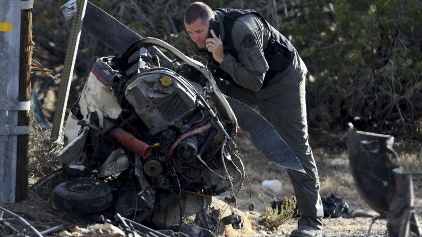A San Bernardino County sheriff's pilot looks over the debris from a fatal plane crash near Hesperia Airport on Friday.