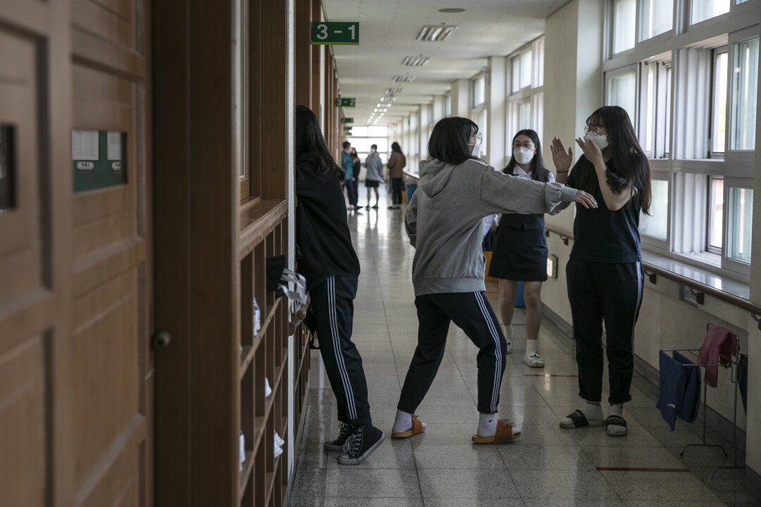 Students at Gyungbuk Girls' High School chat during a break on their first day back in school in Daegu, the city that was at the center of South Korea's coronavirus outbreak.