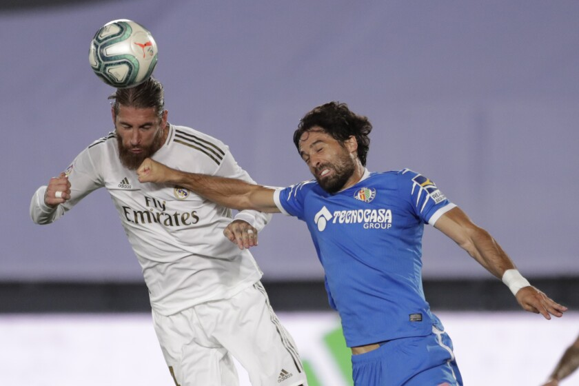 Real Madrid's Sergio Ramos, left, jumps for a header with Getafe's Xabier Etxeita during the Spanish La Liga soccer match between Real Madrid and Getafe at the Alfredo di Stefano stadium in Madrid, Spain, Thursday, July 2, 2020. (AP Photo/Bernat Armangue)