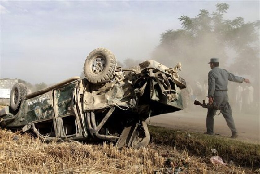 Afghan Police arrive at the site where a police vehicle was hit by a remote control bomb in the Kama district of Jalalabad province, east of Kabul, Afghanistan, Saturday, May 11, 2013. The bomb killed and wounded several policemen, a local government spokesman said. (AP photo/Rahmat Gul)