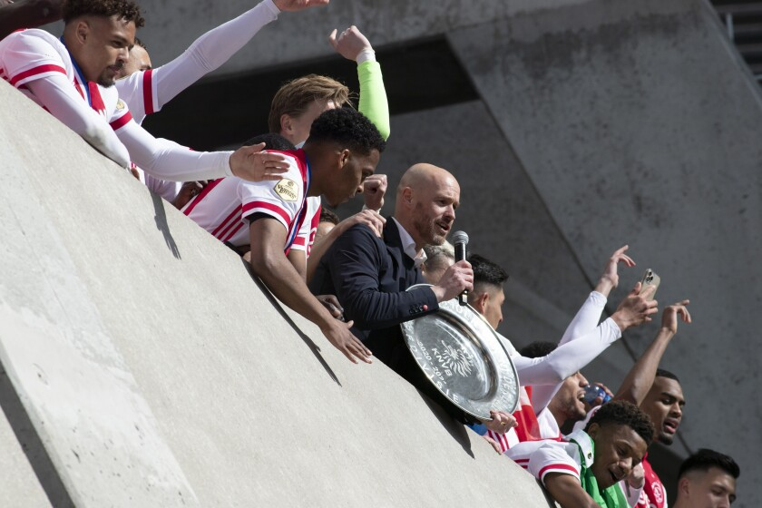 Ajax coach Erik ten Hag, holding the trophy, and players celebrate clinching the Dutch Eredivisie Premier League title after winning the soccer match between Ajax and Emmen with a 4-0 score at the Johan Cruyff ArenA in Amsterdam, Netherlands, Sunday, May 2, 2021. (AP Photo/Peter Dejong)