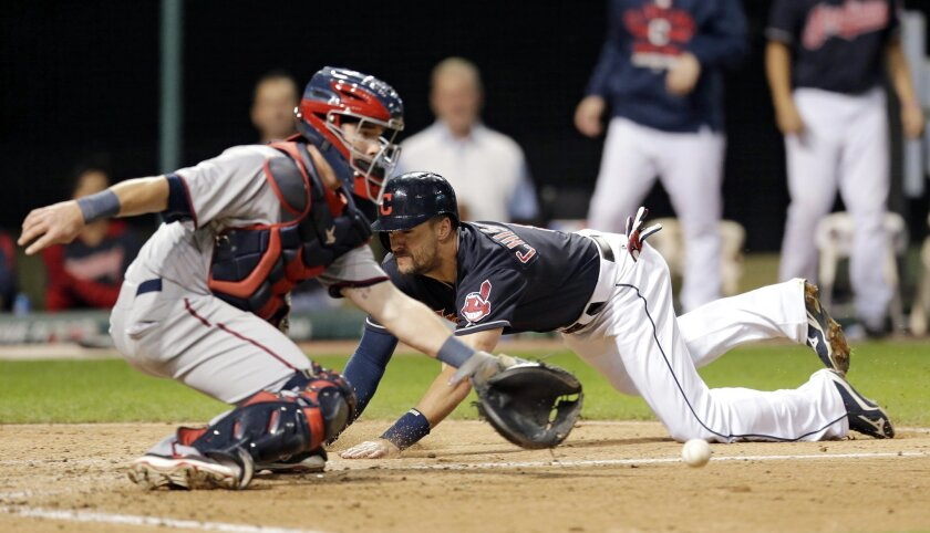 Cleveland Indians' Lonnie Chisenhall scores as Minnesota Twins catcher Chris Herrmann waits for the ball in the third inning of the second baseball game of a doubleheader, Wednesday, Sept. 30, 2015, in Cleveland. Chisenahall scored on an RBI-single by Adam Moore. (AP Photo/Tony Dejak)