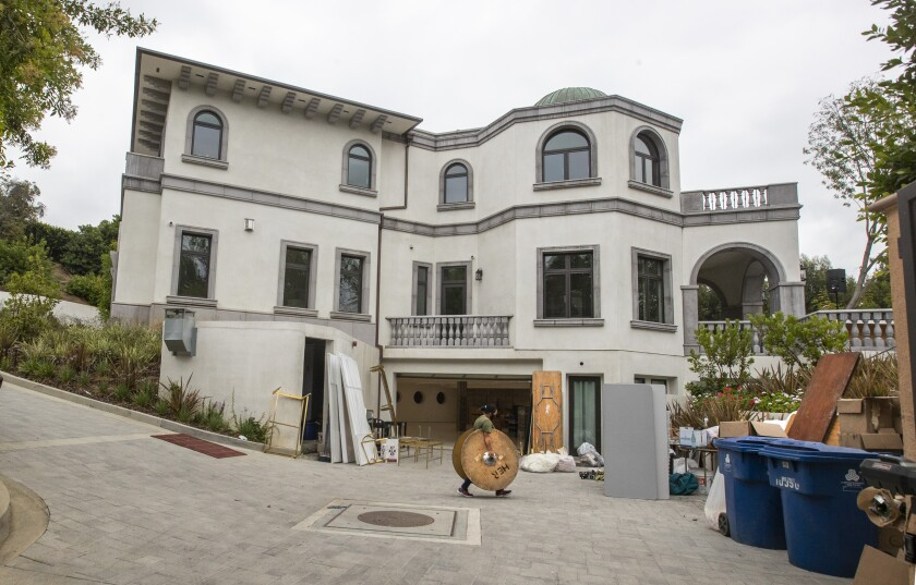 Party rental crews pack up at a home in the 10000 block of Wyton Drive in Holmby Hills