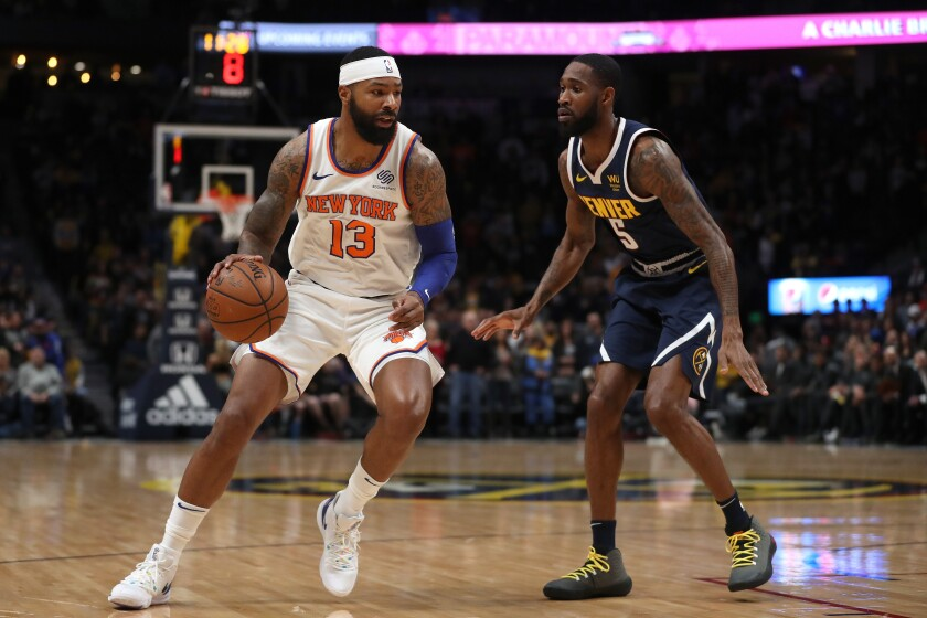 The Knicks' Marcus Morris drives against the Nuggets' Will Barton on Dec. 15, 2019, in Denver.