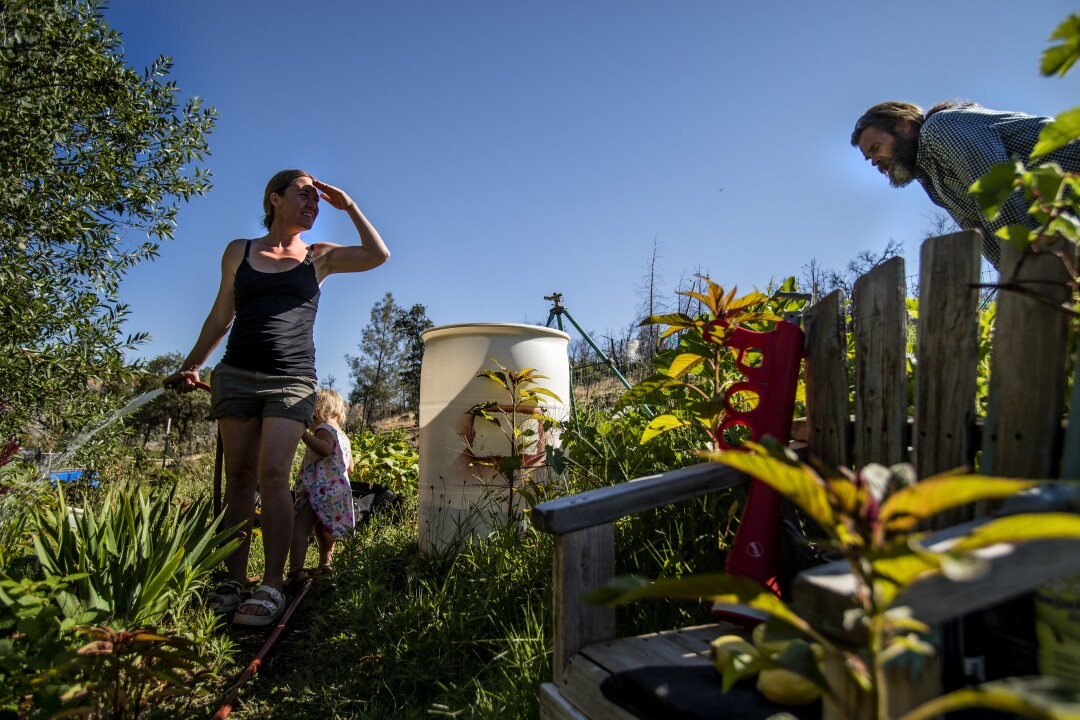 Lacey Nimz, with her young daughter at her side, waters while Mike Nimz bends, inspecting plants.