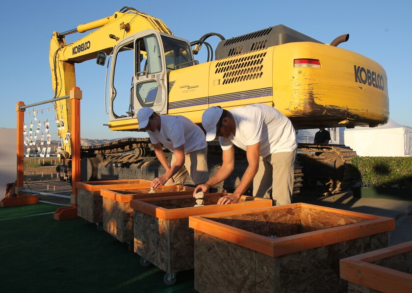 Volunteers organize pieces of the concrete from broken-up runways to be given away as mementos during a recent groundbreaking at the Great Park.