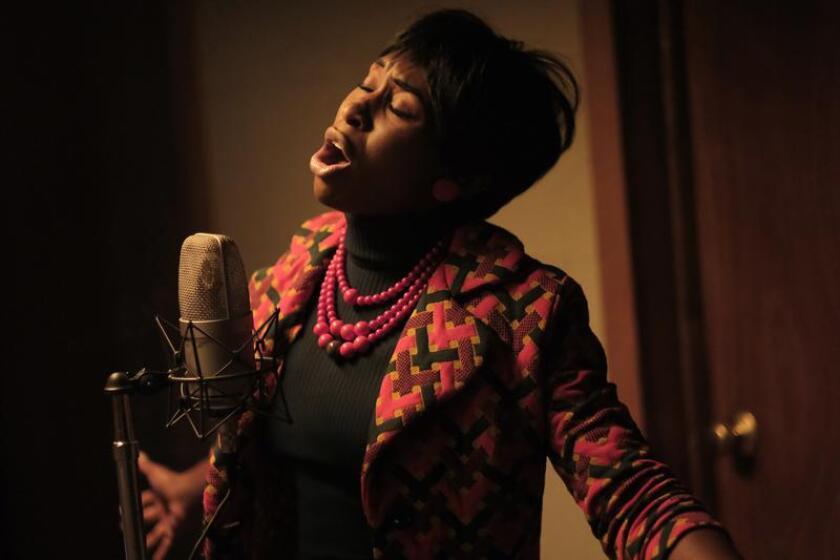 Cynthia Erivo as Aretha Franklin singing into a microphone