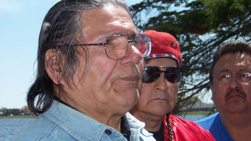 American Indian activist Dennis Banks, left, speaks to reporters on Lake Bemidji, during an American Indian treaty rights protest in Bemidji, Minn., in 2010.