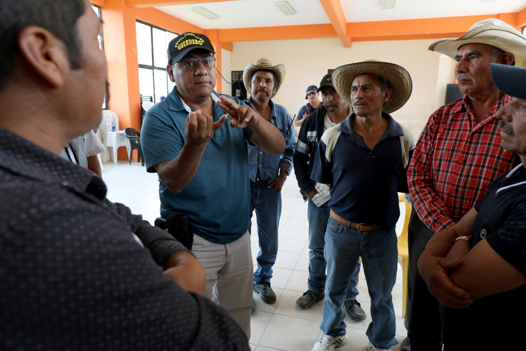 Salvador Alanís Trujillo, second from left, of the United Front of Community Police of Guerrero, meets with poppy farmers in Filo de Caballos. Farmers in Guerrero had been cultivating opium since the 1970s.