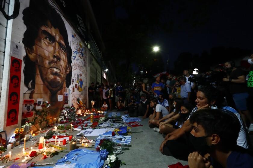 Hinchas acongojados frente a un afiche de Diego Maradona en la entrada de La Bombonera