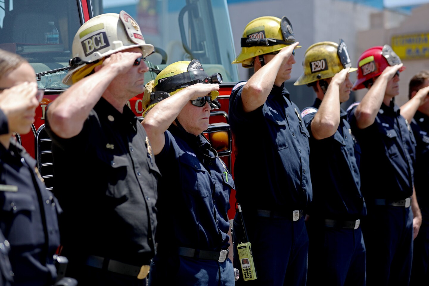 Long Beach firefighters salute as a procession carries Fire Capt. Dave Rosa, 45, to the Los Angeles County coroner's office on Monday.