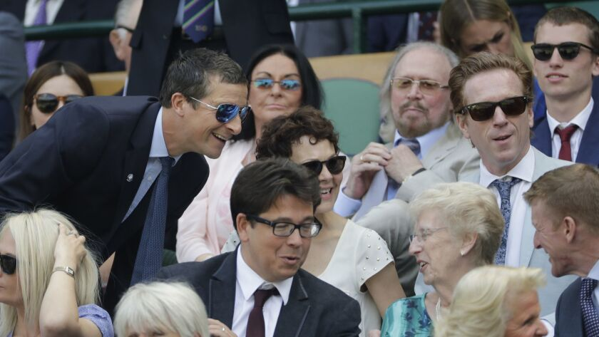 Actors Damian Lewis, right, and Helen McCrory, center, and Bear Grylls, left, sit in the Royal Box o