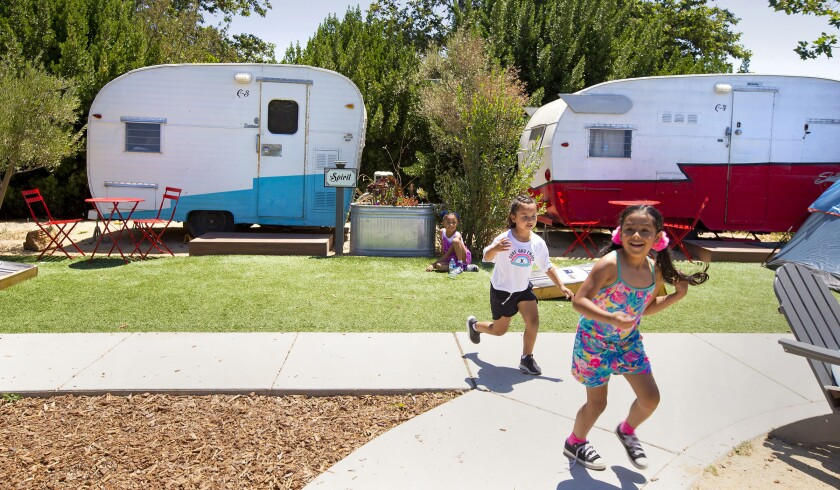 Children play in front of vintage trailers