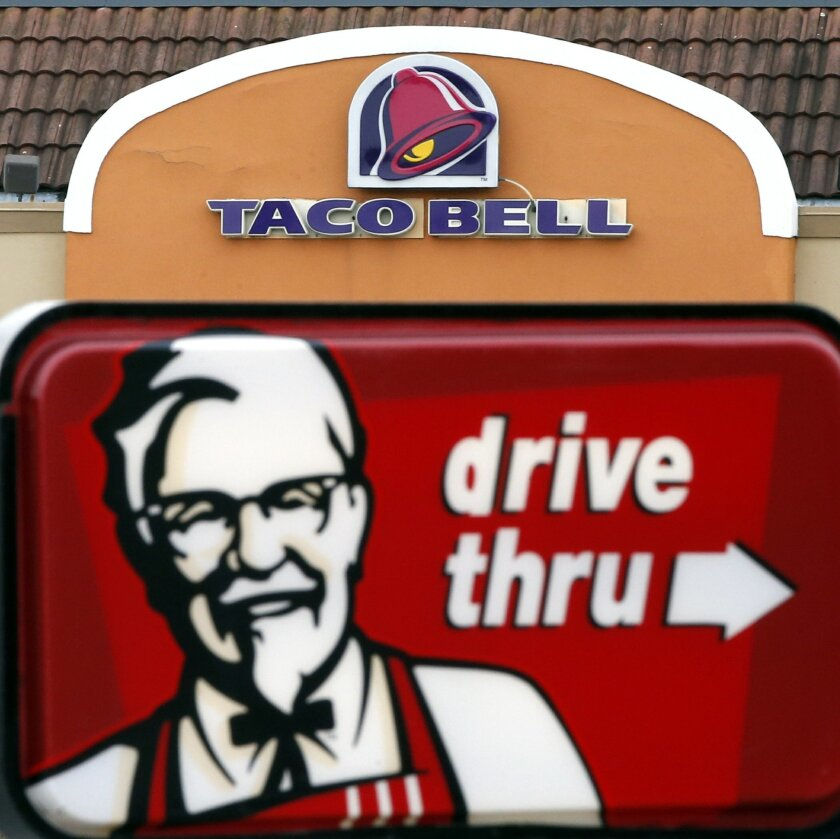 FILE - This Jan. 31, 2014 file photo shows a Taco Bell facade behind a KFC drive-thru sign in Saugus, Mass. Fast-food conglomerate Yum! Brands, Inc., headquartered in Louisville, Ky., reports quarterly earnings on Tuesday, Oct. 7, 2014. (AP Photo/Elise Amendola)