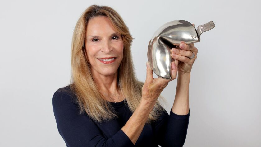 Portrait of artist Maidy Morhous with one of her bronze sculptures that will be displayed in her upcoming exhibit at the Oceanside Museum of Art.