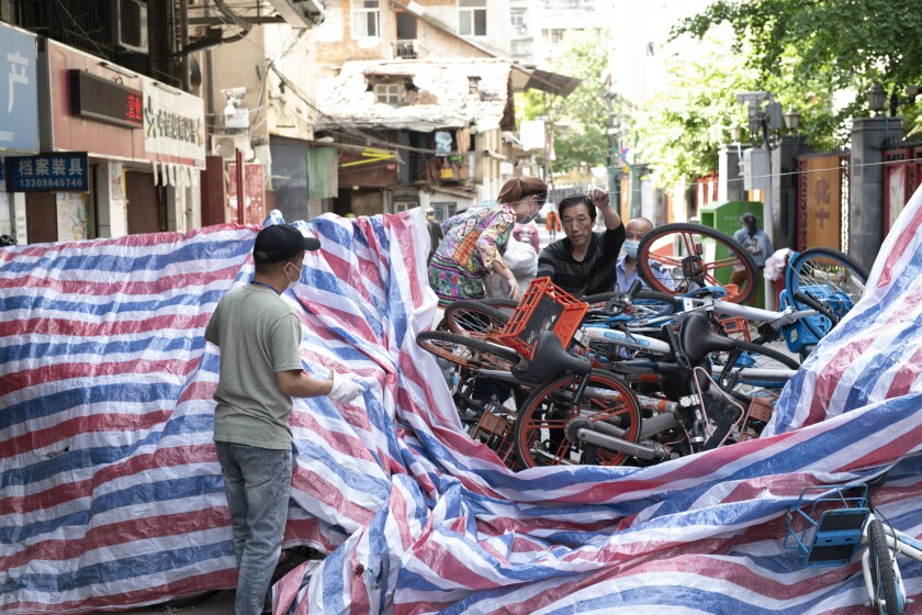 A makeshift barricade of rental bikes and plastic tarpaulin blocks a road in Wuhan. Roadblocks had been part of the lockdown and had finally been removed when the restrictions ended.