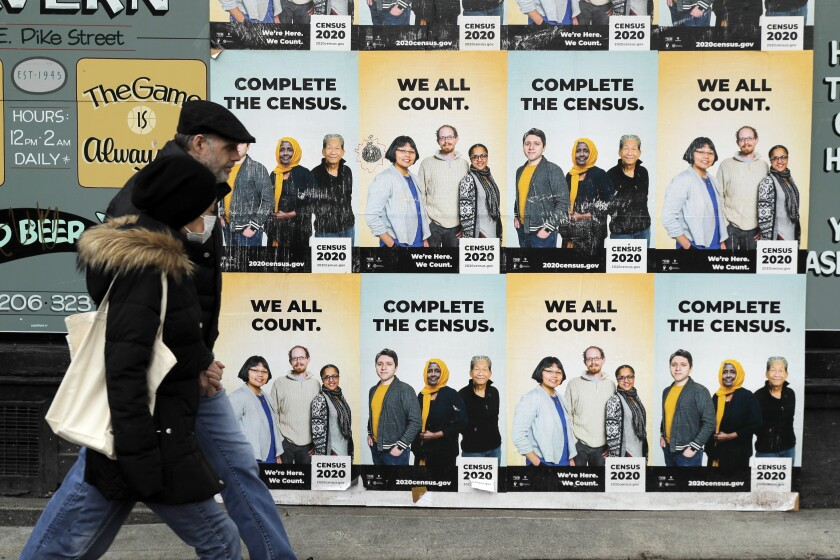People walk past Census 2020 posters on a wall that say Complete the census, we all count.