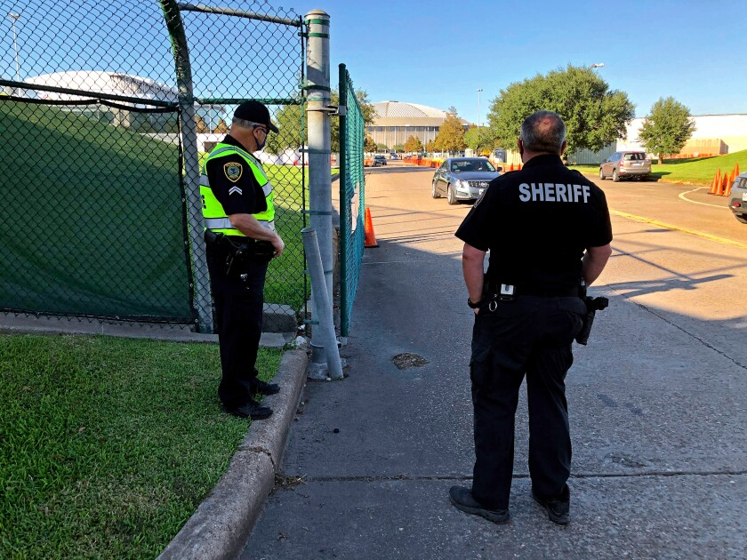 Harris County Sheriff's Deputy R. Hilz and Houston Police Officer T. Jones at a Houston stadium parking lot polling place.