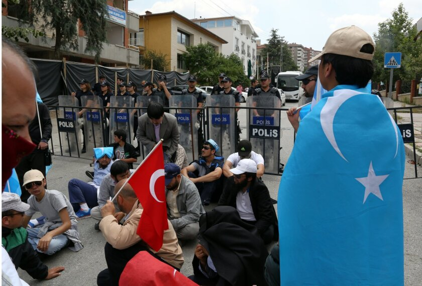 Riot police stand as a group of Uighur protesters demonstrate outside the Thai embassy in Ankara, Turkey, Thursday, June 9. 2015. Thailand sent back to China more than 100 ethnic Uighur refugees on Thursday, drawing harsh criticism from the U.N. refugee agency and human rights groups over concerns