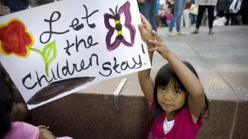 Una pequeña levanta un cartel con un mensaje de apoyo a los niños inmigrantes que actualmente permanecen detenidos y otros enfrentan procesos de deportación.