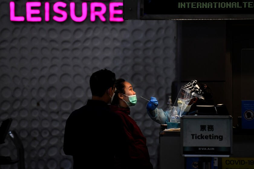 An airline passenger gets tested for the coronavirus near a ticketing sign at Los Angeles International Airport.