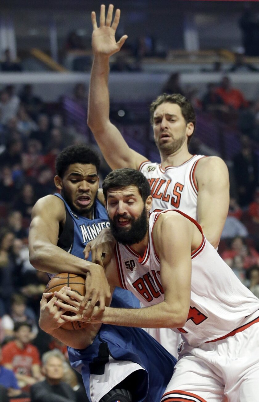 Chicago Bulls forward Nikola Mirotic, right, battles for a rebound against Minnesota Timberwolves center Karl-Anthony Towns, left, as Chicago Bulls forward/center Pau Gasol, center, watches during the first half of an NBA basketball game on Saturday, Nov. 7, 2015,  in Chicago. (AP Photo/Nam Y. Huh)