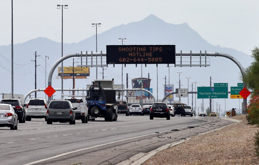 An Arizona Department of Transportation sign gives a hotline number for information on the recent freeway shootings on I-10 in Chandler, Ariz.