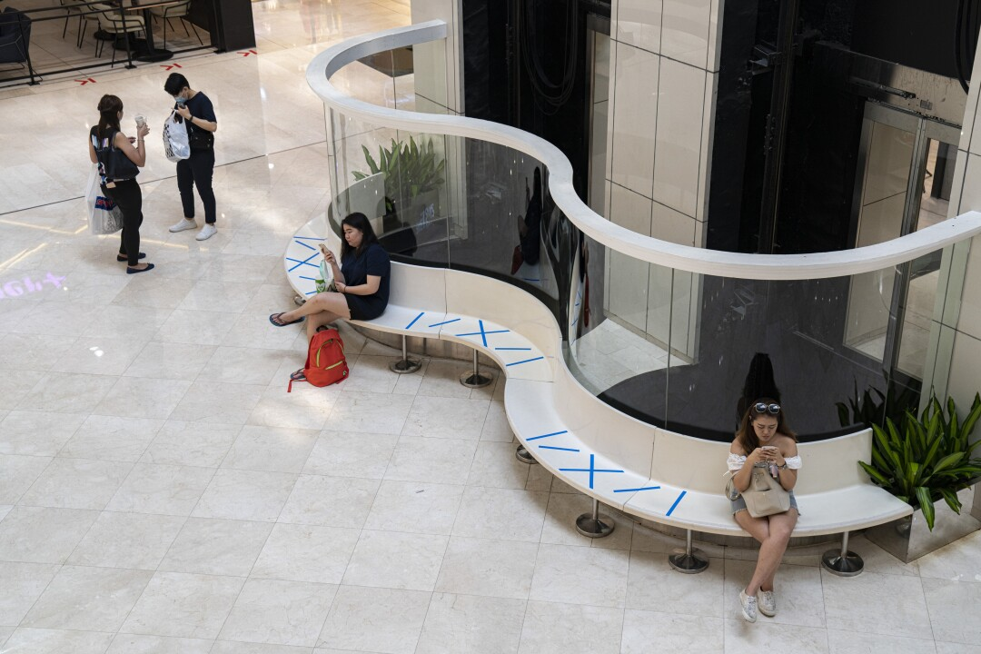 SINGAPORE: People sit along public benches at Wisma Atria shopping mall using safe-distance markers in Singapore. The government there has introduced several such measures to curb the coronavirus spread.
