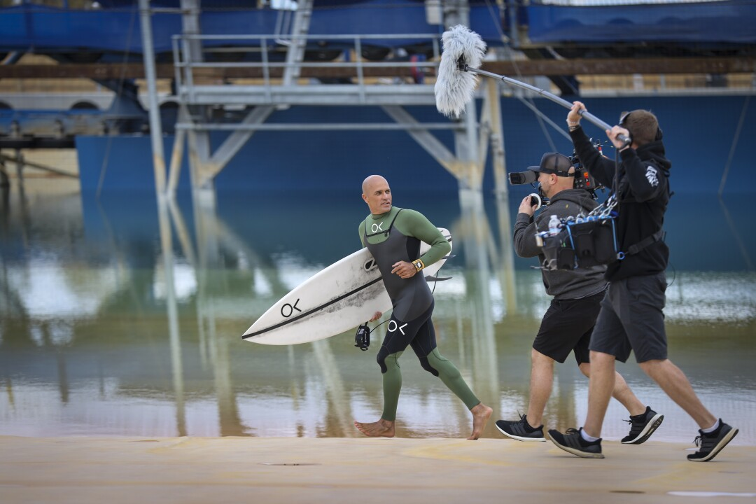 Kelly Slater runs with surfboard in hand as a camera crew follows