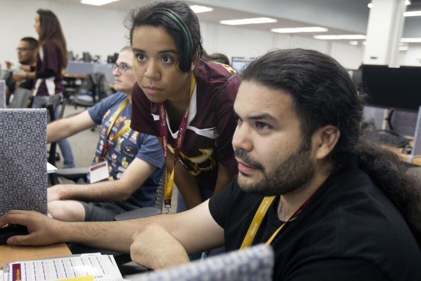 Kiomanie Machon, center, helps Rudy Leyva register for classes during student orientation at Cal State Dominguez Hills. Cal State recently launched a program to help professors find low-cost options for student course materials.
