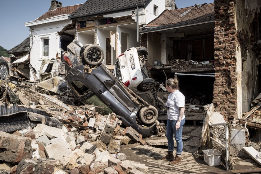 FILE - In this file photo dated Monday, July 19, 2021, a woman looks at cars and homes damaged after torrential rain caused flooding in Liege, Belgium. A new massive United Nations science report is scheduled for release Monday Aug. 9, 2021, reporting on the impact of global warming due to humans. (AP Photo/Valentin Bianchi, FILE)