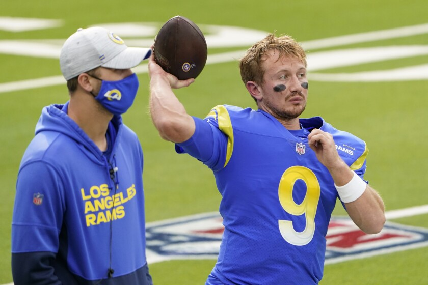 Injured Rams quarterback Jared Goff stands next to quarterback John Wolford before a game.
