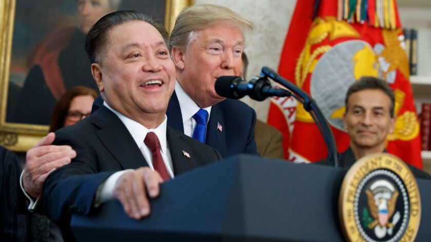 President Trump hugs Broadcom CEO Hock Tan during an event to announce the company is moving its global headquarters to the United States, in the Oval Office of the White House on Nov. 2.