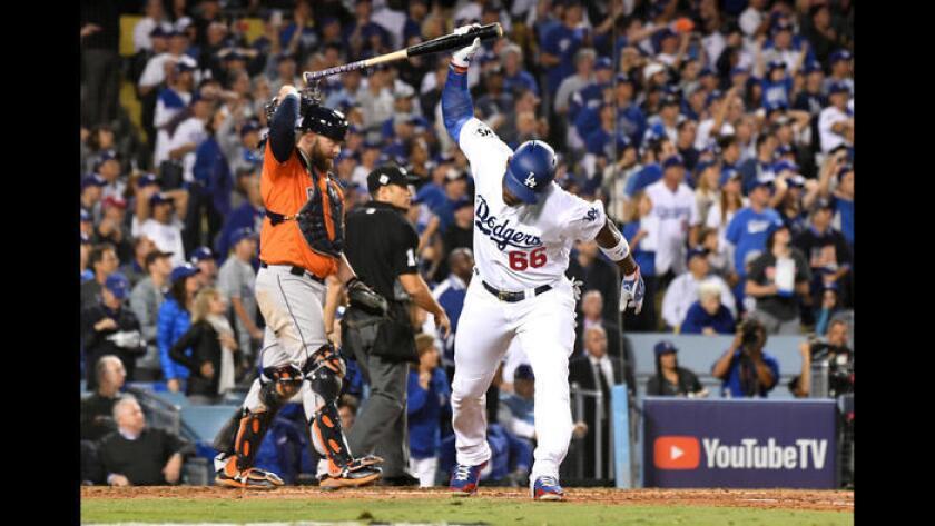 Yasiel Puig de los Dodgers golpea su bate en el suelo después de dejar a dos corredores en base en la tercera entrada. (Wally Skalij / Los Angeles Times)