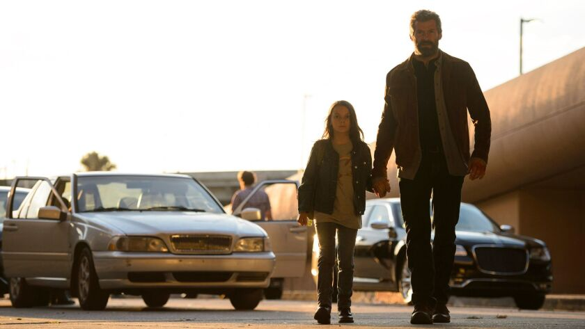"Dafne Keen as Laura and Hugh Jackman as Logan / Wolverine in the film ""Logan."""