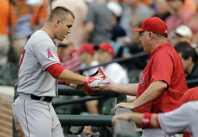 Los Angeles Angels' Mike Trout, left, high-fives manager Mike Scioscia after scoring on a ground out by Josh Hamilton in the first inning of a baseball game against the Baltimore Orioles, Tuesday, July 29, 2014, in Baltimore. (AP Photo/Patrick Semansky)