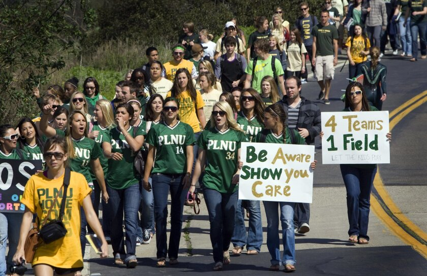 Members of the PLNU softball team lead a march to protest the decision to eliminate four sports, including softball, after this school year. The march ended at the school's former softball field.