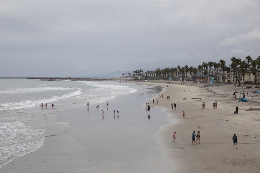 People enjoy the beach near the Oceanside Pier on Thursday in Oceanside.