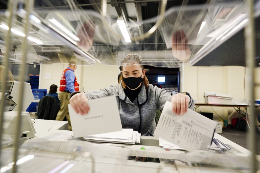 A woman wearing a mask sorts through mail-in ballot envelopes