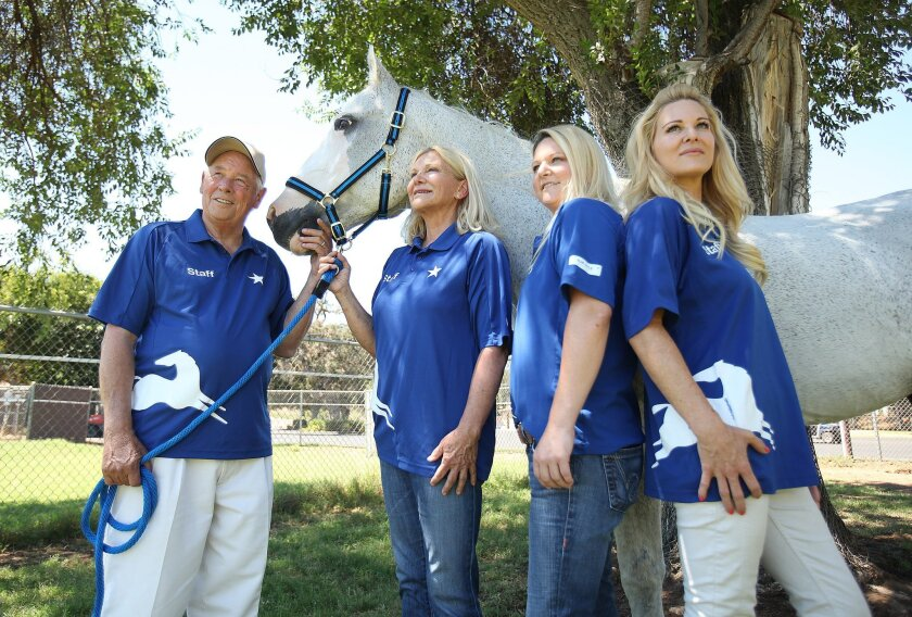 """Blue Apple Ranch, started by the family of Toby Wells, is run by Toby's parents Lloyd Wells, left and Lynn Wells and their daughters April West and Adrienne Holmes. They're pictured here with Gunsmoke, a once-lame horse who has been rehabilitated at the ranch. He's known as the """"Mayor of Blue Apple"""